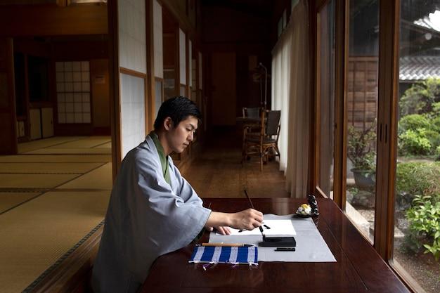 日本語の手書きを練習している男