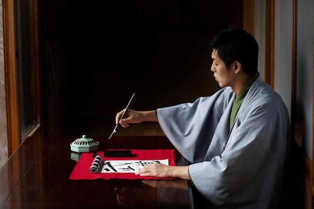 Uomo che pratica la calligrafia giapponese