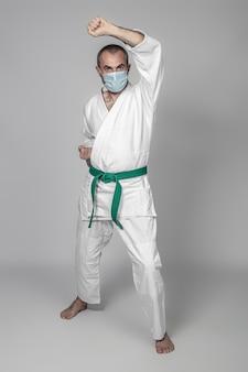 Мужчина занимается боевыми искусствами в хирургической маске для безопасных тренировок во время covid 19