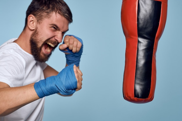 A man practicing a punch on a punching bag in a white t-shirt on a blue background