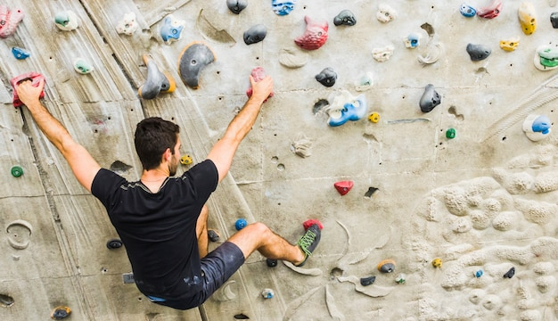 Man practicing rock climbing on artificial wall indoors. active lifestyle concept.