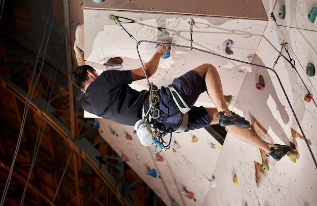 실내 암벽에 암벽 등반을 연습하는 남자