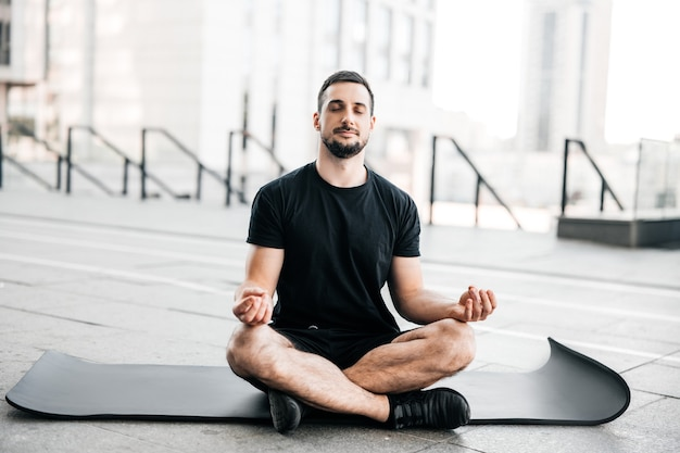 Man practicing yoga in big city. sporty man meditating after workout. excercising at home. young man with stubble sitting on black yoga mat with eyes closed outdoors and relaxing in easy seat pose.