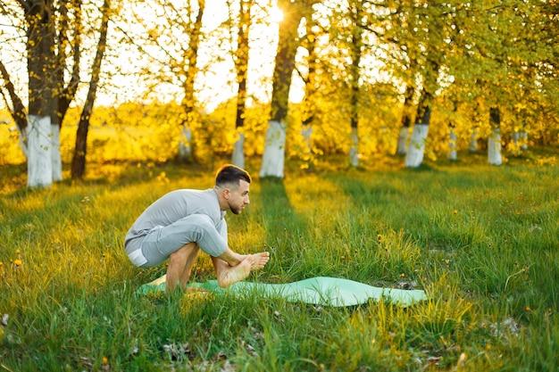 아름 다운 석양 공원에서 요가 연습하는 남자. 건강한 생활