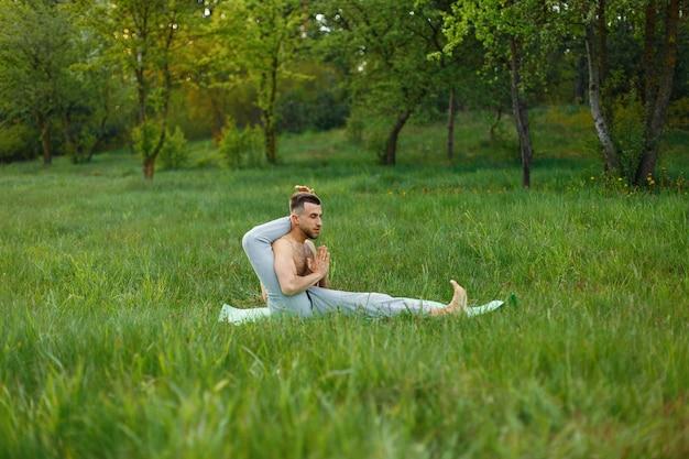 Человек, практикующий йогу в траве на открытом воздухе