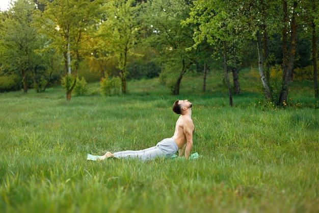 공원에서 잔디에 요가 연습하는 남자