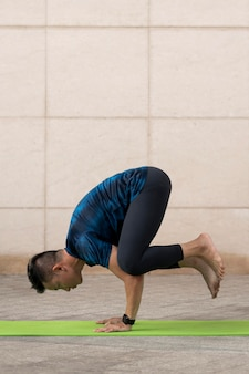 Человек, практикующий йогу на открытом воздухе на коврике