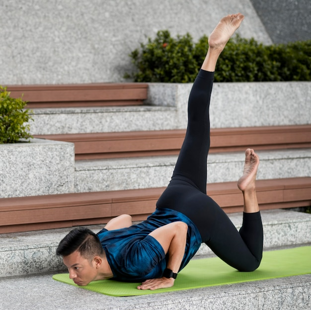 Man practicing yoga outdoors on steps