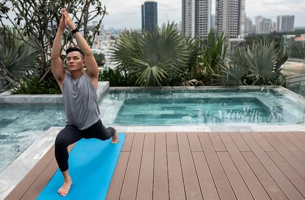 L'uomo a praticare yoga all'aperto con copia spazio