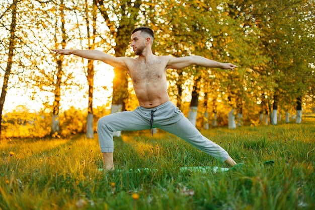 Man practicing yoga in the spring park at sunset. healthy lifestyle
