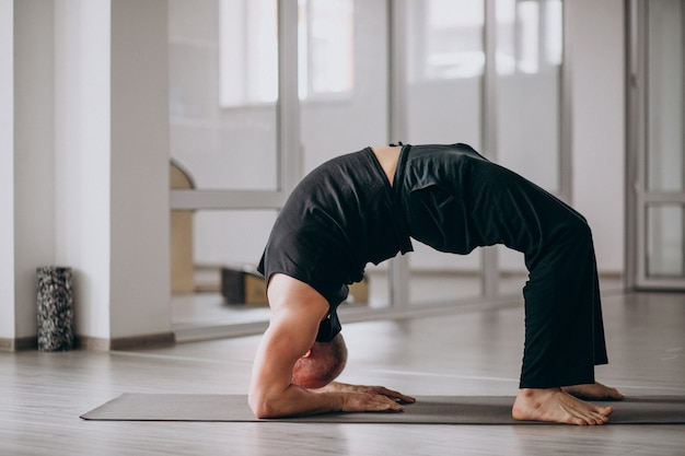 Man practising yoga in the gym