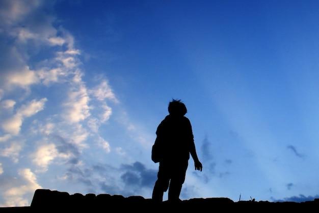 日没の山で一人で祈る男旅行ライフスタイル精神的なリラクゼーション感情的な概念