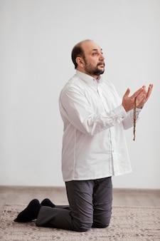 Uomo che prega sul pavimento al chiuso