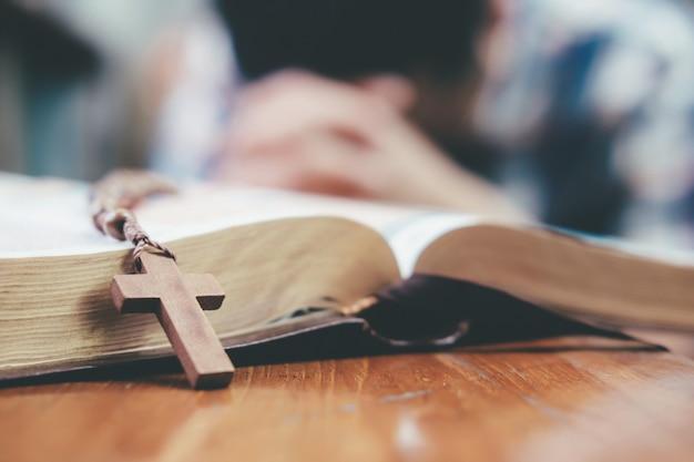 기도하는 사람, 그녀의 성경에 손을 함께 쥐었다.