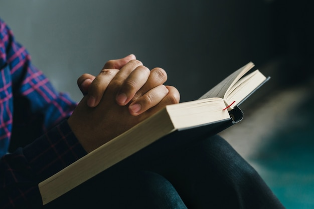 Man praying on holy bible in the morning.teenager boy hand with bible praying,christians and bible study concept.copy space