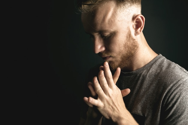 Человек молится на черном