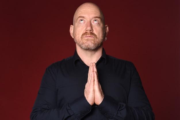 Человек молится на красном фоне, посмотрите вверх