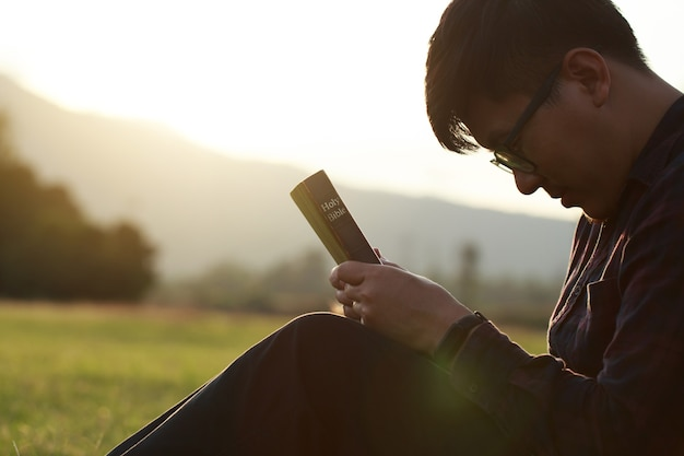 目を閉じて座っている美しい日没の男性の間にフィールドで聖書を祈る男