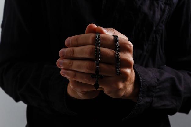 남자는 검은 배경에 십자가와 함께기도