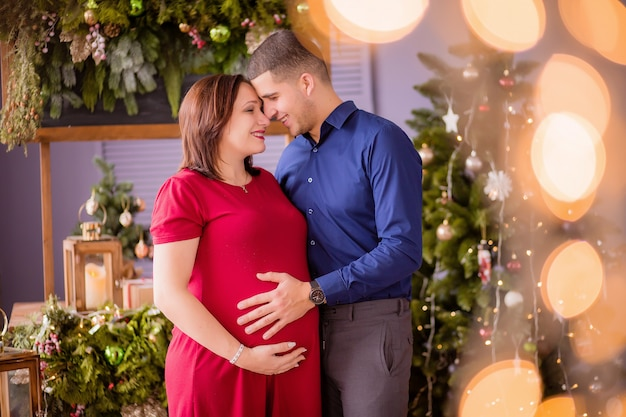 Man and a pregnant woman next to the christmas tree