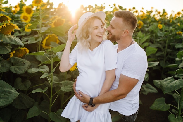 Man and pregnant woman hug each other tender standing in the field with tall sunflowers around them