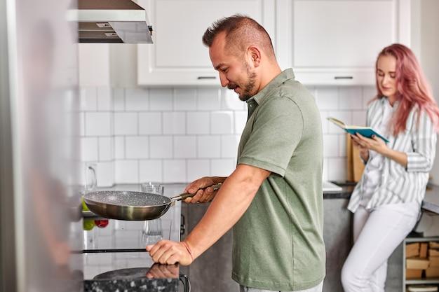 男は朝食を準備し、週末に自宅でカップル、明るいモダンなキッチンで美しいカップル