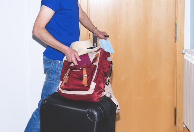 Man prepared to leave for a trip after confinement with passport, suitcase and backpack. hand gel and mask. copy space.