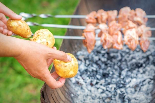 감자와 바베 큐 고기를 준비하는 남자