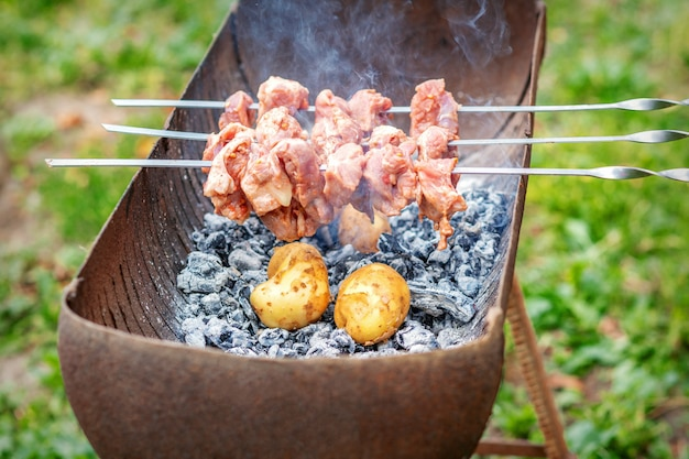 Man prepares barbecue meat with potatoes