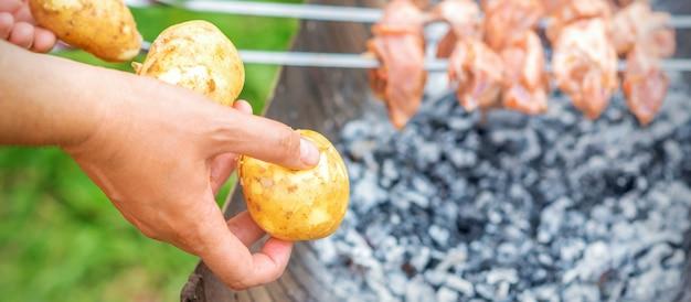 Мужчина готовит шашлык из мяса с картошкой