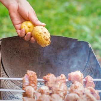 Мужчина готовит барбекю мясо с картофелем