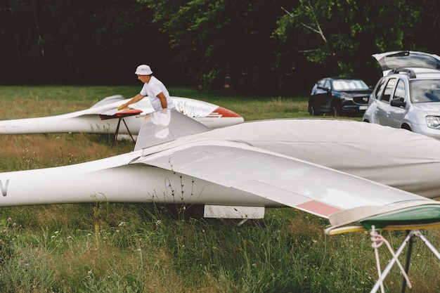 Man prepares and checks gliders parked in the field