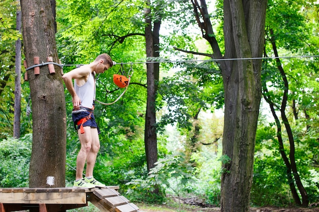 Человек готовится подняться по канатам в парке
