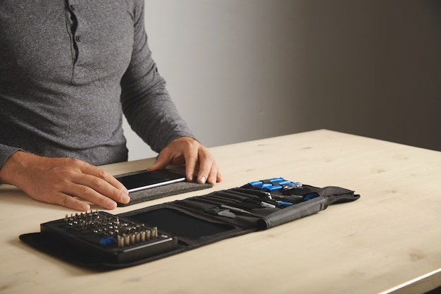 Человек готовится разобрать телефон дома со своим личным портативным набором инструментов на столе. место для текста справа.