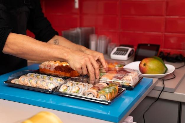 テイクアウトの寿司注文を準備している男