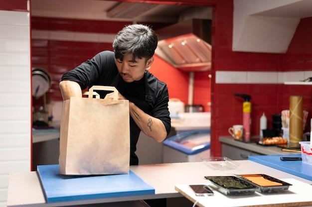 Мужчина готовит заказ суши на вынос