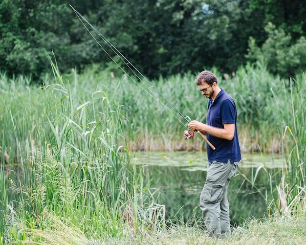 魚を捕まえるために釣り竿を準備する男