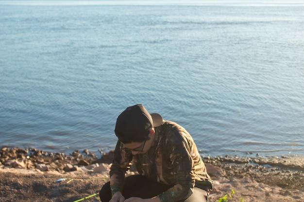 Мужчина готовит удочку на берегу реки.