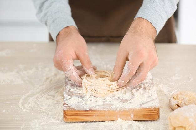 Человек готовит макароны на кухонном столе