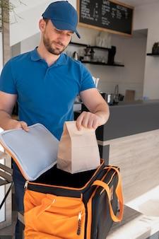Man preparing takeaway food for delivery