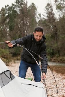 キャンプ用のテントを準備している男