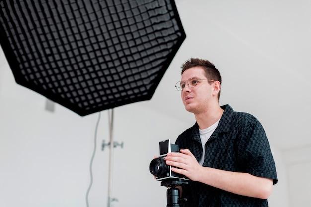 Мужчина готовит студию к съемкам и смотрит в сторону