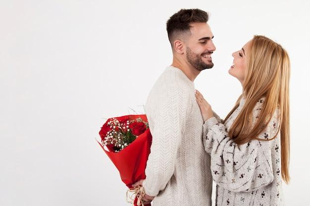 Человек готовится передать цветы женщине