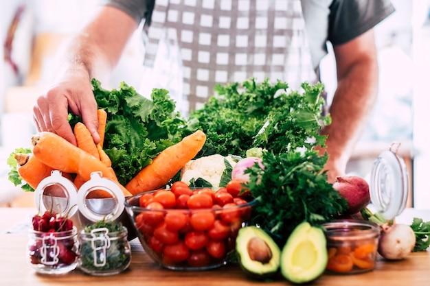 Мужчина готовит вегетарианскую и веганскую еду - стол, полный свежих сезонных здоровых овощей - сочетание цветов и витаминов - сосредоточиться на руке, принимая морковь - концепция оздоровительного образа жизни