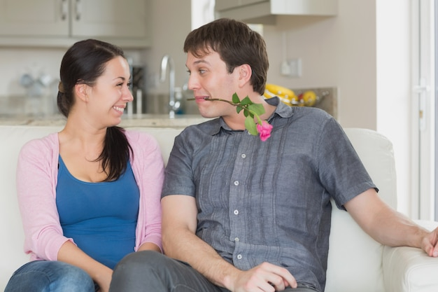 Man presenting a flower to the woman in his teeth