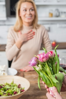 Man presenting flowers to surprised woman in kitchen