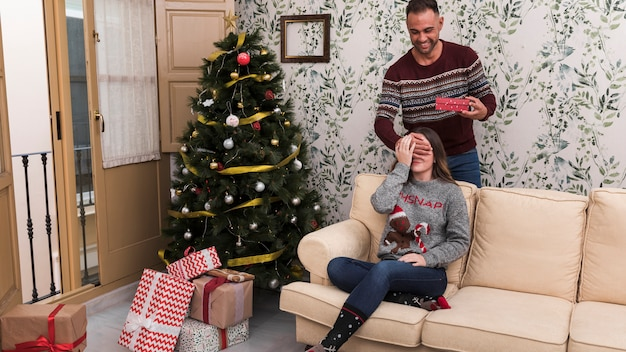 Man presenting gift box and closing eyes to woman on settee near christmas tree
