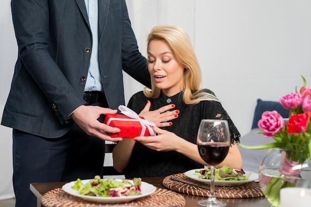 Человек, представляя подарочную коробку изумленной женщине за столом