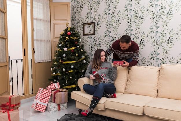 Man presenting gift box to woman on settee near christmas tree