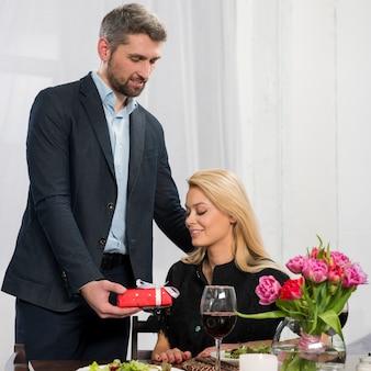 Man presenting gift box to woman at table